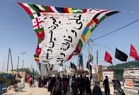 رفع راية تحمل أعلام الدول والجنسيات المشاركة في زيارة الأربعين