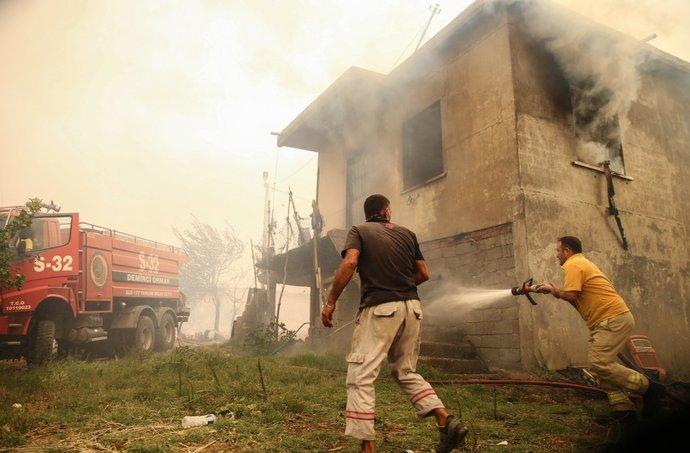 آتش نشان و شهروند محلی در حال خاموش کردن آتش در