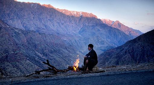 آتش مرد چوپان در غروب پلنگان و کنار جاده آسفالتی که به این روستا می رسد. Amos Chapple
