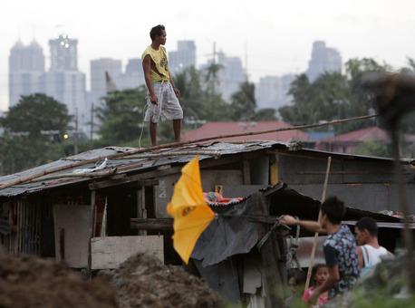 مردی بر بام خانه اش به ویرانی های بجای مانده از طوفان