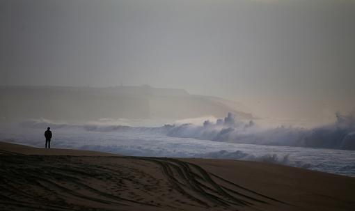 فردی در انتظار برگشت پلیس دریایی در ساحل مِکو در نزدیکی سسیمبرا (پرتغال) روز یکشنبه هفت جوان برای تفریح به این ساحل رفته بودند که گرفتار موج دریا شده و دو تن از آنان (یکی مرده و دیگری مجروح) توسط امدادگران یافت میشوند و پنج تن دیگر هنوز ناپدید هستند. REUTERS/Rafael Marchante