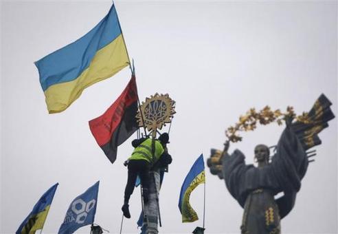 تظاهرات ضد دولتی مردم اوکراین همچنان در کییف ادامه دارد. مردی از پایه فلزی (درخت کریسمس) بالا رفته تا نماد ملی این کشور را بیاویزد. CREDIT: REUTERS/GLEB GARANICH
