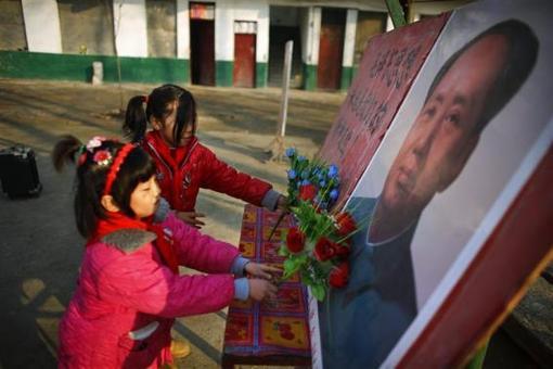 دو دانشآموز در حال ادای احترام با گذاردن دسته گل در کنار پرتره مائوتسهتونگ؛ رئیسجمهور فقید چین که از وی به عنوان پدر سیاست و اقتصاد این کشور به نیکی یاد میشود. REUTERS/CARLOS BARRIA