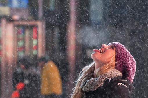 یکی از گردشگران سعی می کند تا هنگام بارش برف در میدان تایمز نیویورک، دانه های برف را روی زبان خود نگه دارد-REUTERS/Darren Ornitz