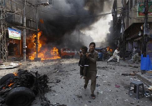 مردی در حال دور کردن کودک از محل انفجار یک بمب در پاکستان