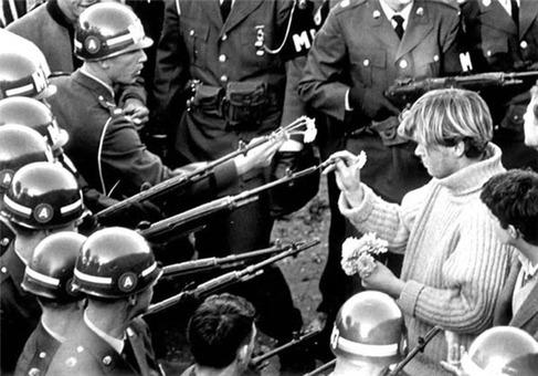 تظاهرکنندگان در سال 21 اکتبر 1967 بعد از راهپیمایی رویداد پنتاگون در اسلحه های نیروهای مسلح گل میگذارند