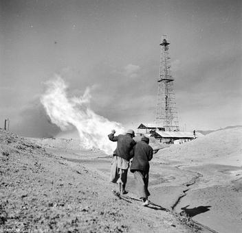 عکس مربوط به سال ۱۳۳۲ دو کارگرشرکت نفت را نشان میدهد که ظاهراً خود را از حرارت آتش نفت محافظت میکنند!