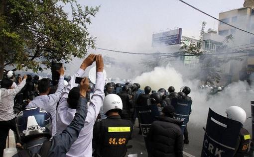 نیروهای امنیتی کامبوج معترضان را با شلیک گاز اشک آور متفرق کردند. / شینهوا