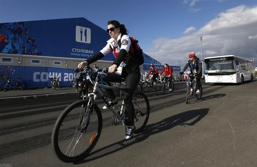 قهرمان کانادایی، سوار بر دوچرخه از محل دهکده المپیک در حال عبور است