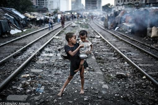 برنده جایزه محیط زیست - عکس از دو کودک میان ریل راه آهن در بنگلادش - آلودگی محیط زیست و تراکم جمعیت فقیران در دو سوی ریلها و پرسپکتیو عالی عکس از ویژگیهای انتخابی این تصویر می باشد
