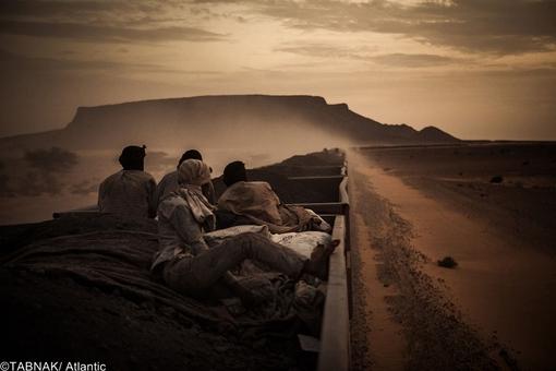 برنده از اسپانیا- معدنچیان نشسته بر واگن حمل سنگ آهن در صحرای موریتانی
