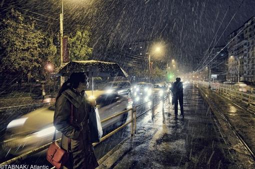 یک زن زیر باران شدید و رگبار ایستاده در ایستگاه تراموا در بخارست