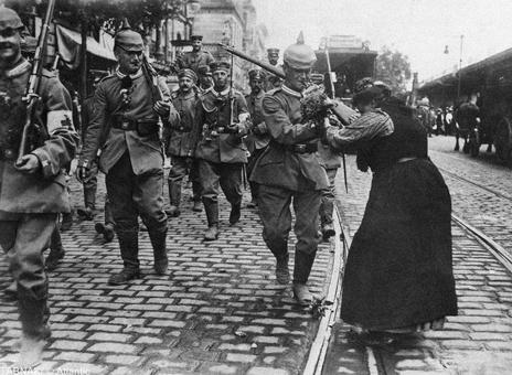سال ۱۹۱۴ - پیاده نظام گارد پروس در حال ترک برلین، آلمان، به سمت خط مقدم جبهه. دختران و زنان در طول راه به  بدرقه آنها رفته و دست گل به سربازان اهدا می کنند