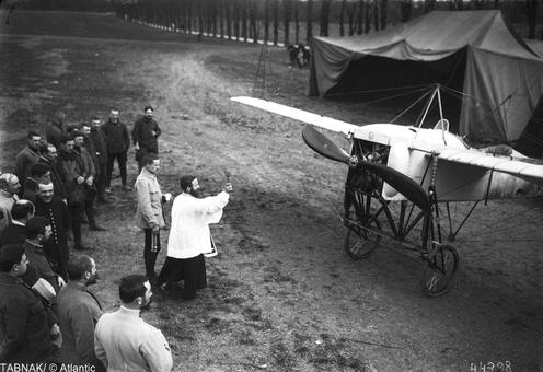 سربازان فرانسوی در کنار کشیش برای پرواز برکت آمیز هواپیمای جدید دعا می کنند در سال ۱۹۱۵