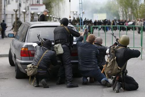 عکس: جداییطلبان هوادار روس مسلح هستند (در تصویر گروهی از آنها در نزدیکی یکی از مراکز پلیس در لوهانسک). در حالی که غرب دور تازهای از تحریمها را علیه روسیه اعمال کرده است، جداییطلبان هوادار آن کشور در اوکراین همچنان به پیشرفتهای خود ادامه داده و در تازهترین تحولات چندین ساختمان دولتی را در شهر «لوهانسک» تصرف کردهاند.دفتر استانداری و دادستانی در این شهر از جمله مراکزیاند که روز نهم اردیبهشت ماه به تصرف جداییطلبان که گروهی از آنها مسلح هستند، درآمدهاند./Reuters-RFE/RL