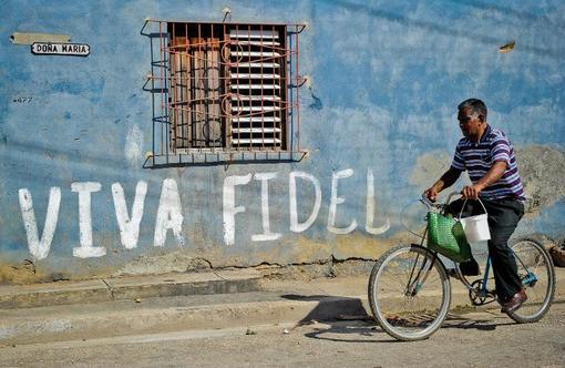 یک خیابان در هاوانا و مرد دوچرخه سوار از مقابل اسم فیدل کاسترو میگذرد./AFP
