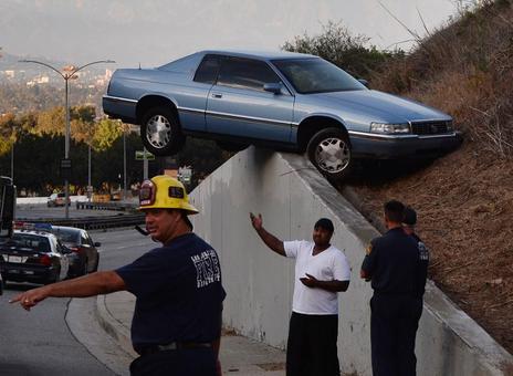 قرار گرفتن عجیب یک خودرو در شانه بتونی بزرگراهی در لس آنجلس/AFP