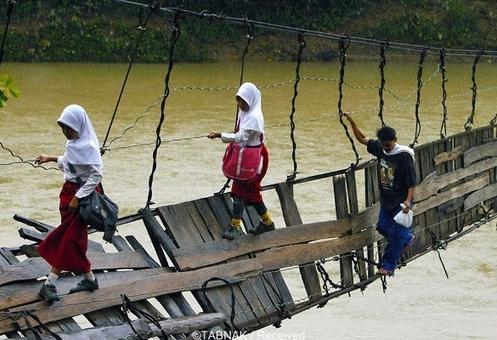 این دانش آموزان اندونزیایی در منطقه « لیبک» قرار دارند و باید برای مدرسه رفتن از روی این پل معلق و آسیب دیده رد شوند.