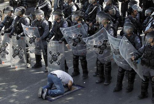 اقامه نماز یک فلسطینی در مقابل نیروهای پلیس رژیم صهیونیستی در بیت المقدس./afp