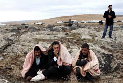 آوارگان سوری در مرز ترکیه، از شدت سرما پتو به دور خود پیچیده و به کوبانی و مبارزه کردها با تکفیریها نگاه می کنند./epa