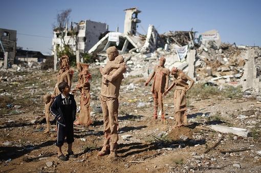 کودک فلسطینی در حال نگاه کردن به مجسمه هایی است که توسط ایاد صباح، هنرمند فلسطینی، در خرابه های بجا مانده از جنگ اخیر غزه ساخته شده است. این مجسمه ها نماد آوارگان فلسطینی است که در حال گریز از خانه هایشان هستند./reuters-euronews