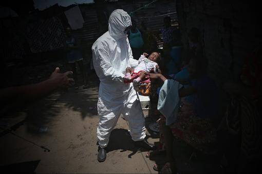 غرب منقطه مونروویا در لیبریا وکنترل یک خانواده مشکوک به ویروس ابولا توسط نیروهای کادر پزشکی و امدادی./ getty images