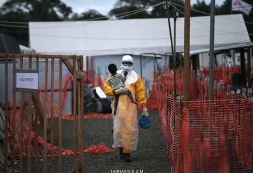 کارمند اداره بهداشت در لیبریا، کودک بیمار را در آغوش کشیده است.