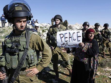 عکسی در رویترز منتشر شده که ظاهراً زن فلسطینی که در تظاهراتی در اعتراض به شهرک سازیهای صهیونیستها حضور یافته، نشان میدهد. وی دستنوشتهای که بر روی آن کلمه صلح نوشته را در میان سربازان عصبانی ارتش رژیم غاصب صهیونیست در نزدیکی بیت الحم نشان میدهد. این عکس مورد توجه رسانههای غربی قرار گرفت. /REUTERS<br /><br />