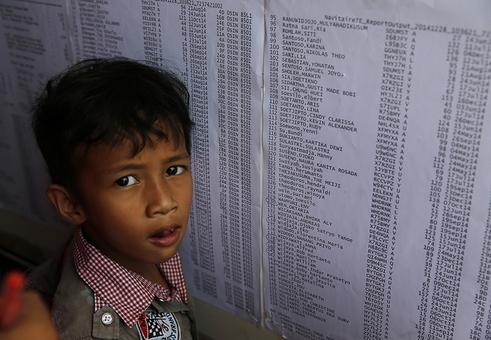 در فرودگاه سورابایا، کودکی در کنار فهرست مسافران بدنبال نام عمه اش می گردد. هواپیمای خطوط هوایی ایرآسیا روز یکشنبه در مسیر هوایی بین سورابایا و سنگاپور ناپدید شد./REUTERS<br /><br />