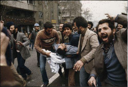 تظاهر کننده مجروح را به سمت آمبولانس میبرند