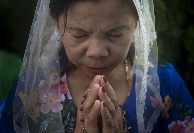 دعا و نیایش زن کاتولیک میانماری در بیرون از یکی از کلیساهای این کشور،پیش از آنکه پاپ فرانسیس به این کشور وارد شود.