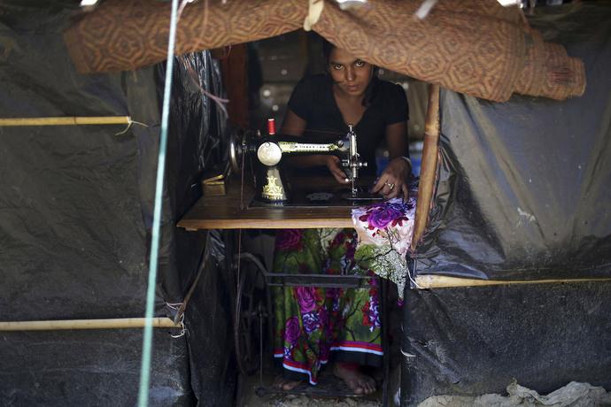 بانوی روهینگیایی که در کمپ آواره گان در بنگلادش در حال کار با چرخ خیاطی است.