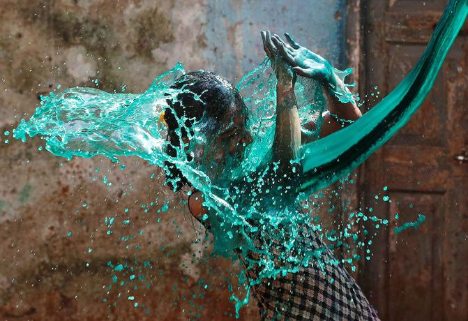 دختری در بمئی هند در جشنواره رنگ ها؛زیر موجی از آب های رنگین