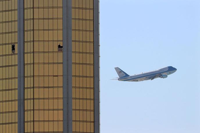 عبور هواپیمای رئیس جمهور آمریکا از کنار هتلی با پتجره های شکسته در لاس وگاس؛پنجره های شکسته مربوط به اتاقی است که از آنجا یک نفر به روی مردم شلیک کرد و 58 نفر را کشت و 547 نفر را مجروح کرد.