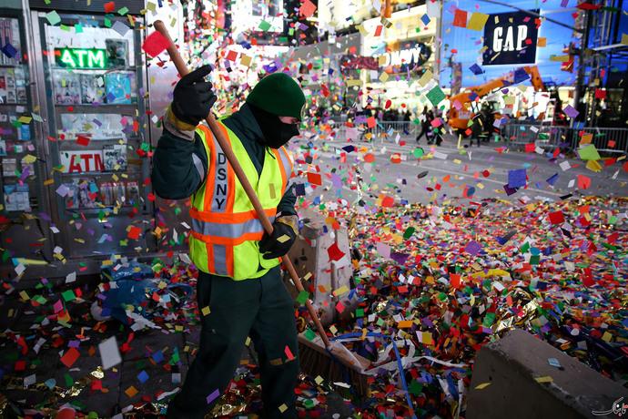 رفتگری که در میدان تایمز نیویورک زیاله های بر جا مانده از جشن سال نو را جمع اوری می کند.