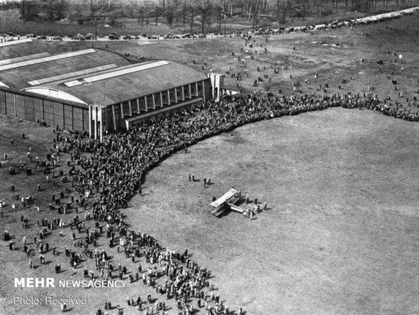 یک هواپیما در مقابل جمعیت زیادی از مردم در فرودگاهی در منچستر انگلستان فرود می آید