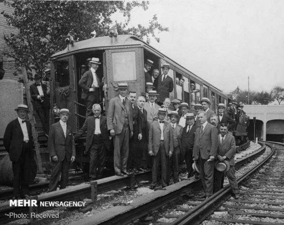 عکسی از مقامات کمیسیون بین شهری و خدمات عمومی نیویورک در کنار یک قطار مترو در زمان افتتاح نشان داده می شود